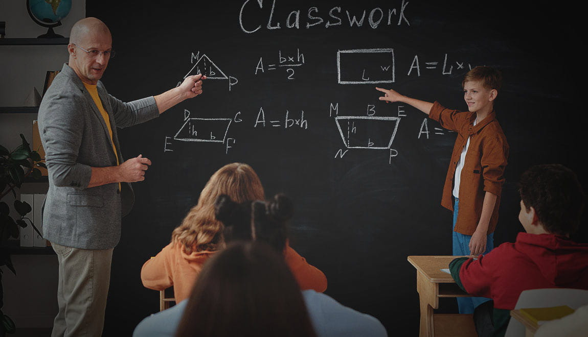 Teach and student at blackboard in the classroom