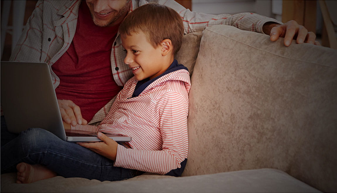 Father and young boy sitting on a couch looking at a computer