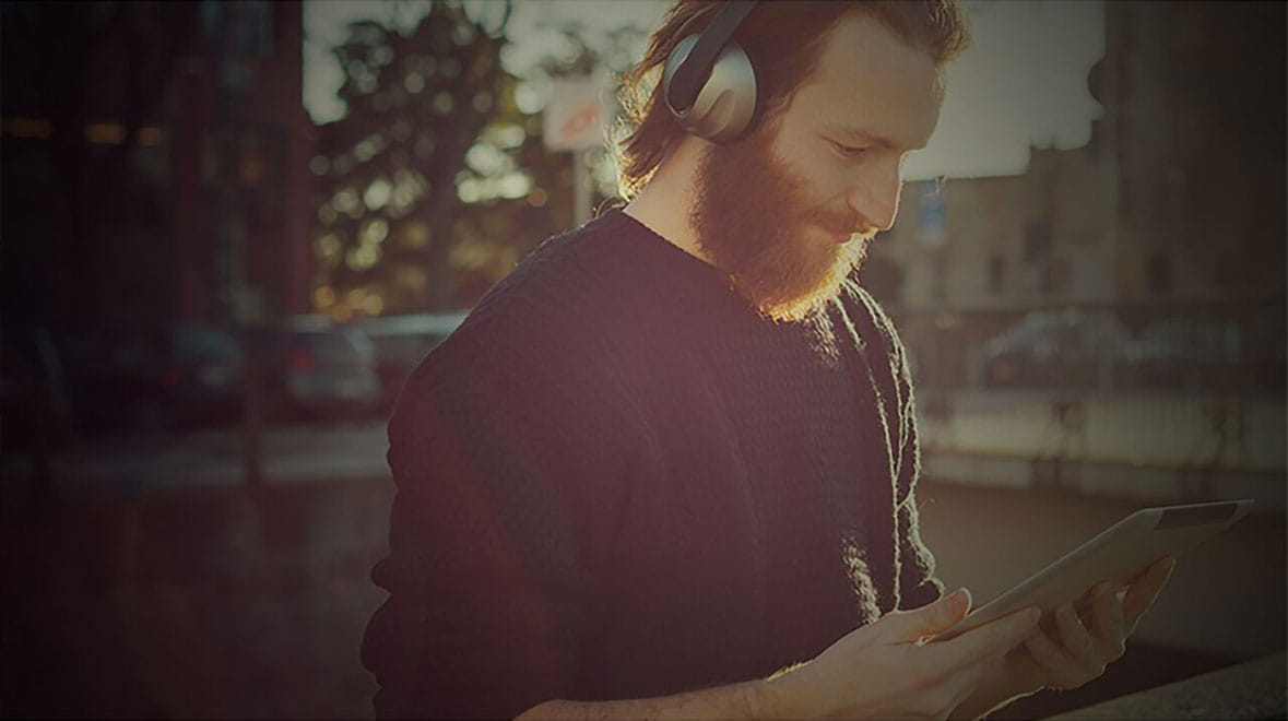 Bearded man wearing headphones and looking at a tablet