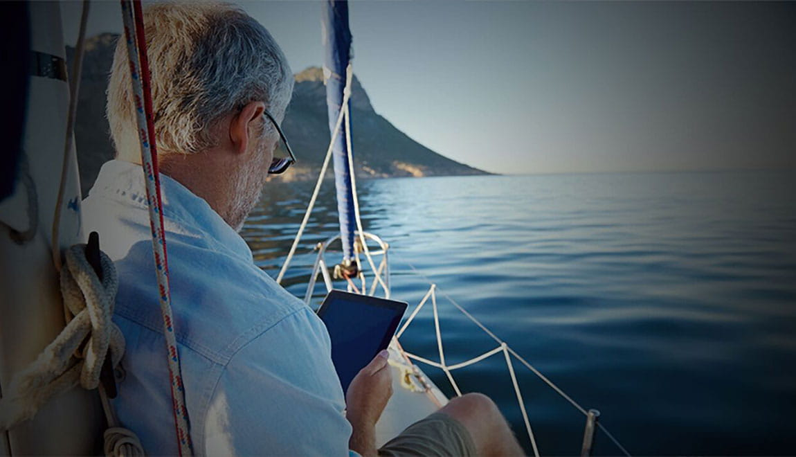 Older man relaxing on a sailboat while looking at a tablet