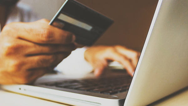 person entering credit card info on laptop