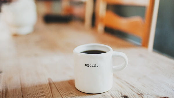 Full coffee cup on table with 'begin' written on the side