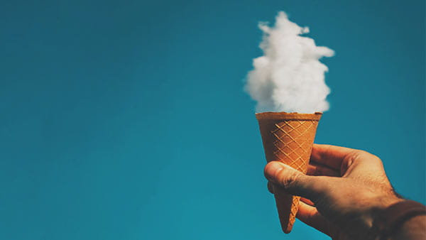 Hand holding an ice cream cone with a cloud in it